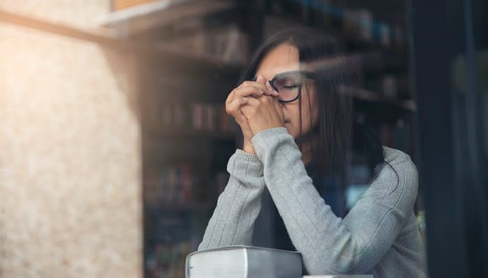 woman with hands folded on Bible praying