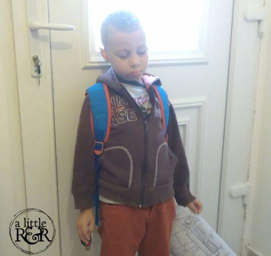 child standing in front of door looking sad