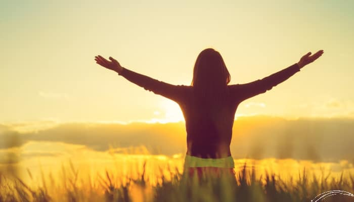 Woman in field with hands raised