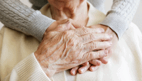 Persons hands on the heart of an elderly person caring for them